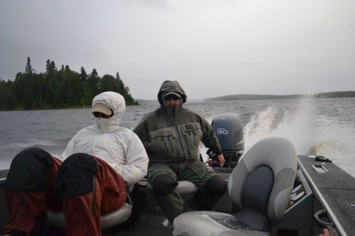 Ben Beattie pilots the boat through the inclement weather of Northwestern Ontario's Lac Seul.