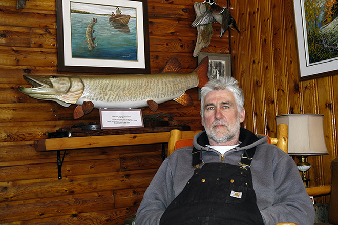 Vermilion Bay Lodge owner Gord Bastable sits in front of a wooden replica of the biggest muskie caught in Eagle Lake — a 61-pounder Edward Walden caught in 1940.