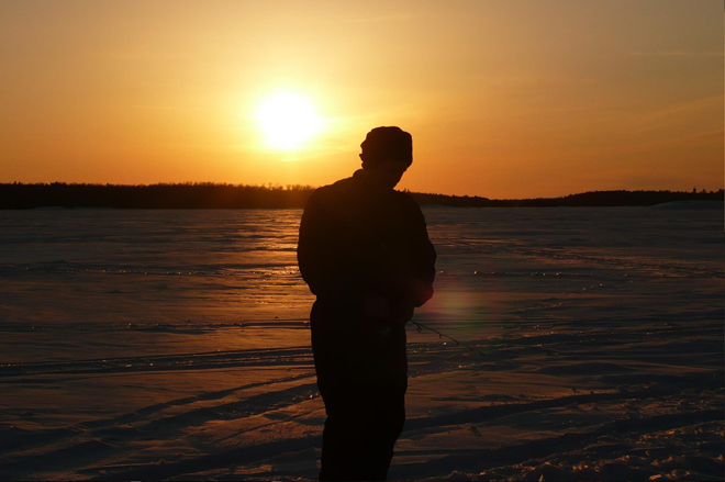 An ice fisherman at Harris Hill Resort on a frozen Lake of the Woods