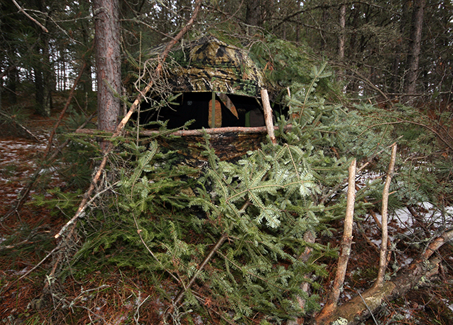 A ground blind should have natural branches and cover around it to help conceal it from deer.  Also, notice the shooting rail in front of the window to help aid steady shots.