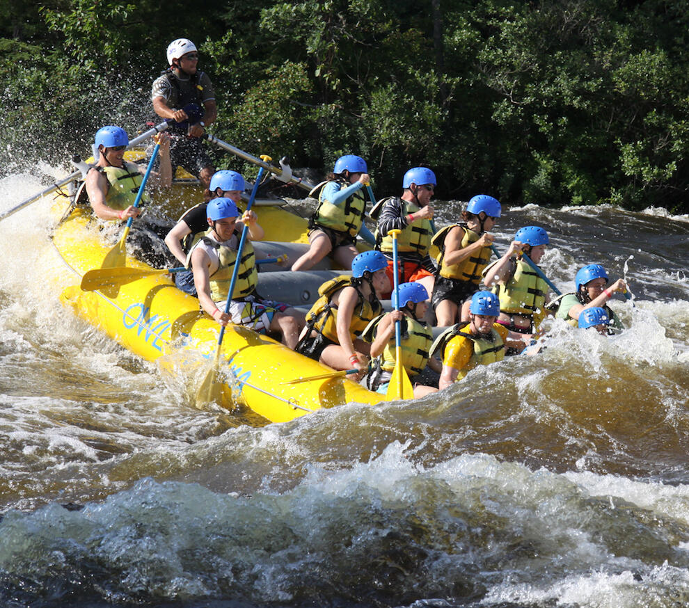 Group of people paddling a 12 person raft in whitewater.