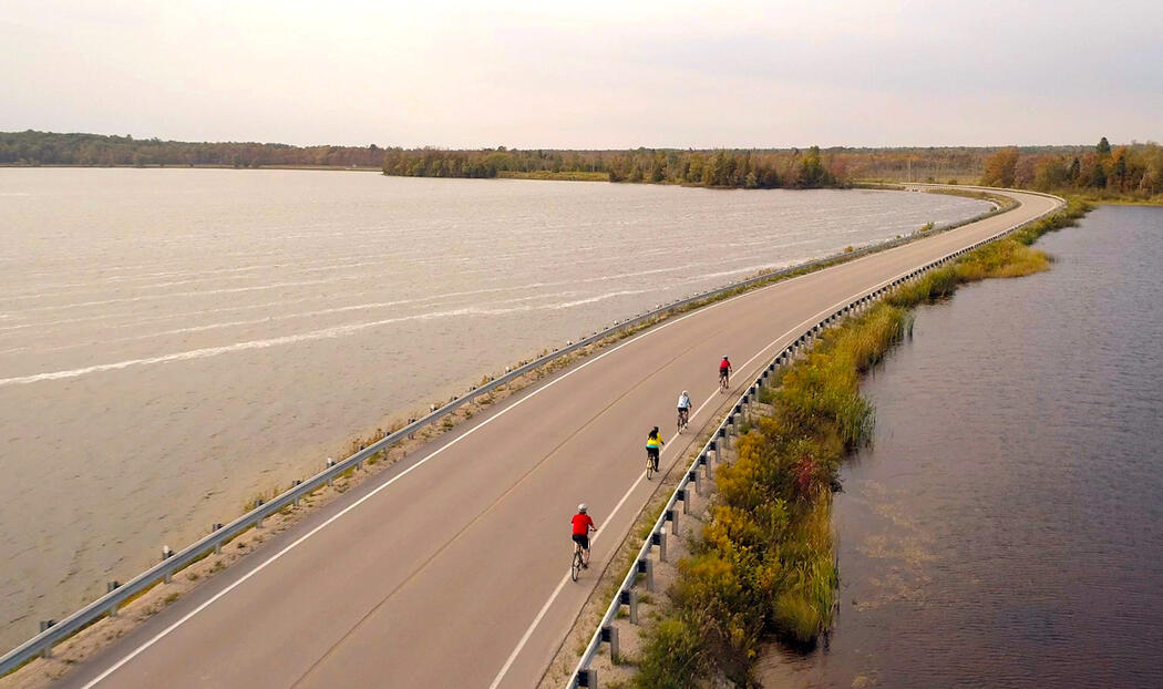 Group of cyclists riding on a paved causeway.