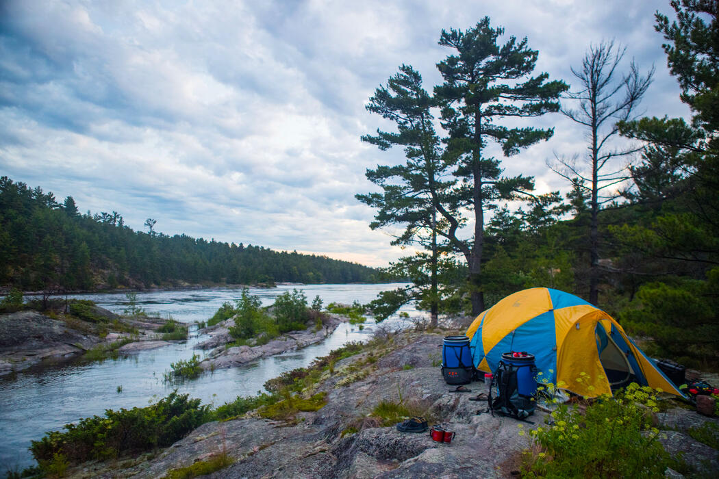 Tent set up on a smooth rock shoreline along a river.