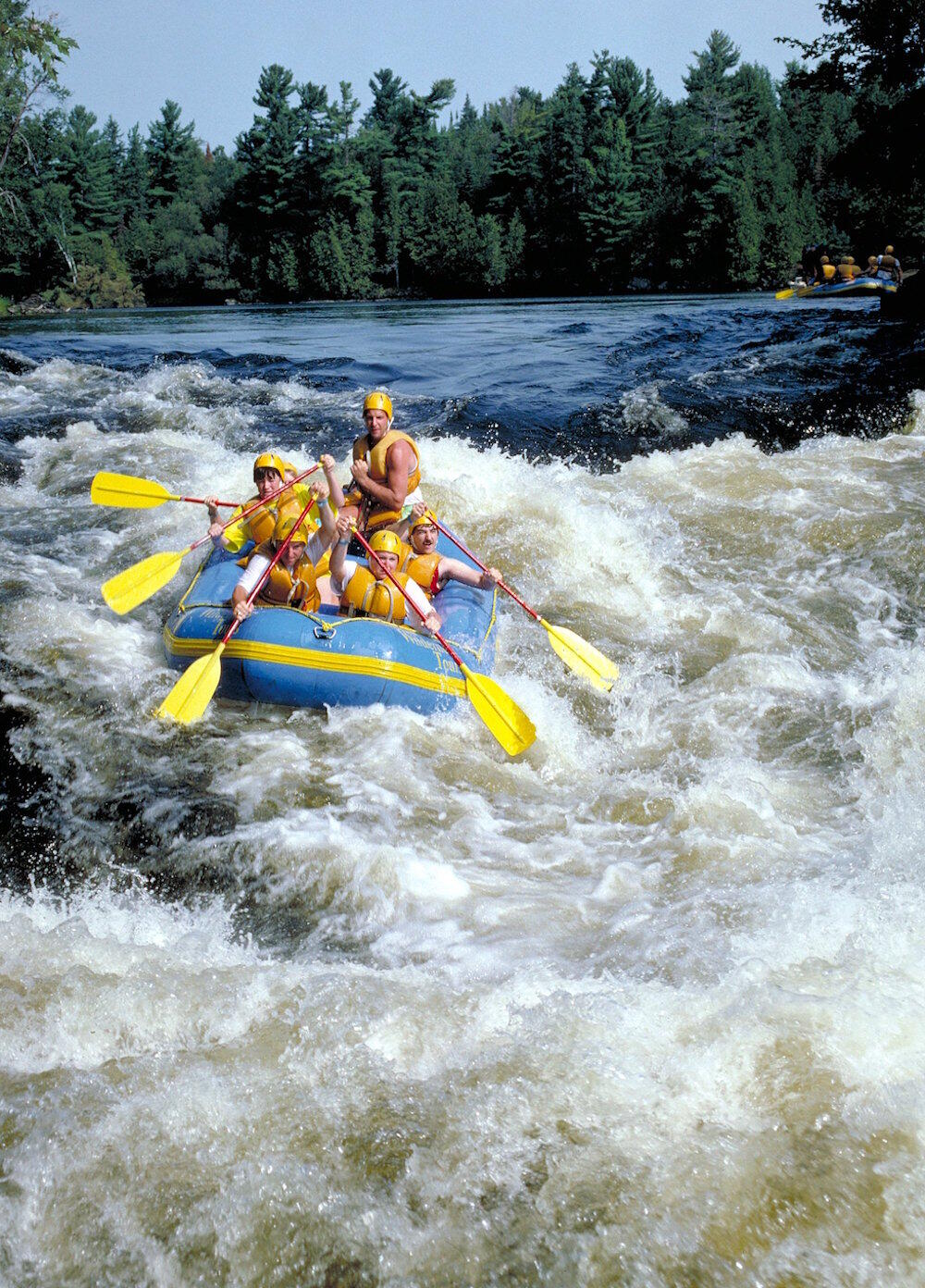 6 people paddling a small raft in white water rapids