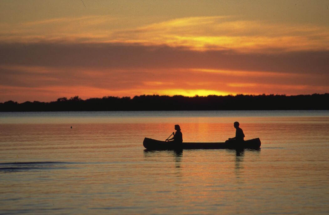 Two people paddling a canoe at sunset.