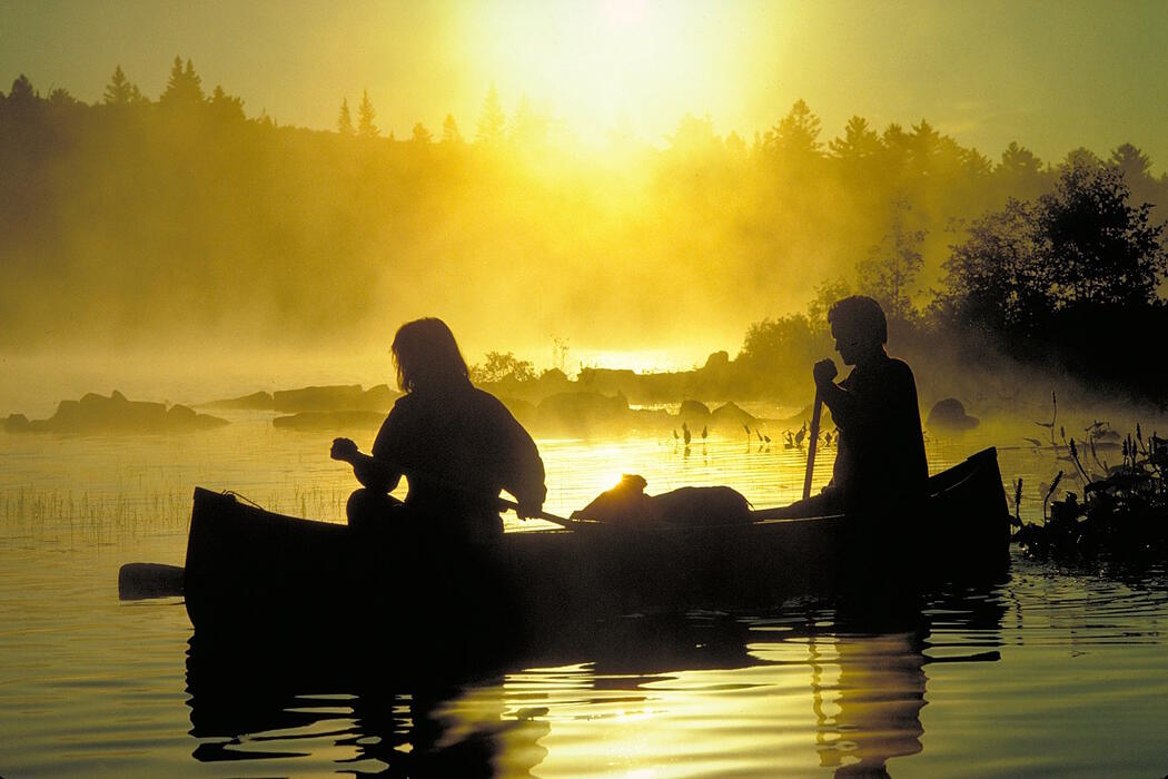 Two people in a canoe in the early morning misty sunrise.