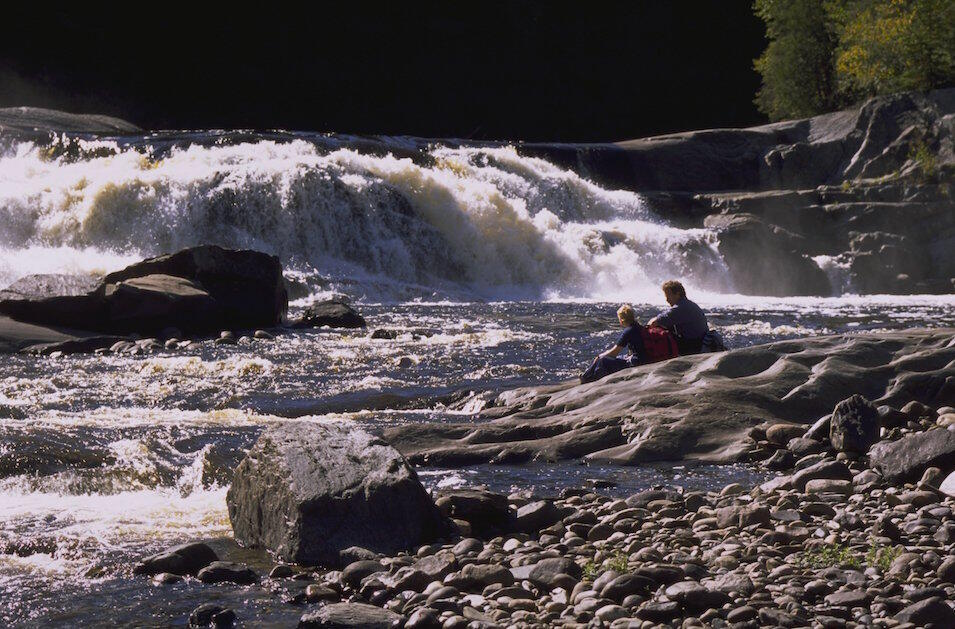 Two people sitting on a rock looking a a small waterfall