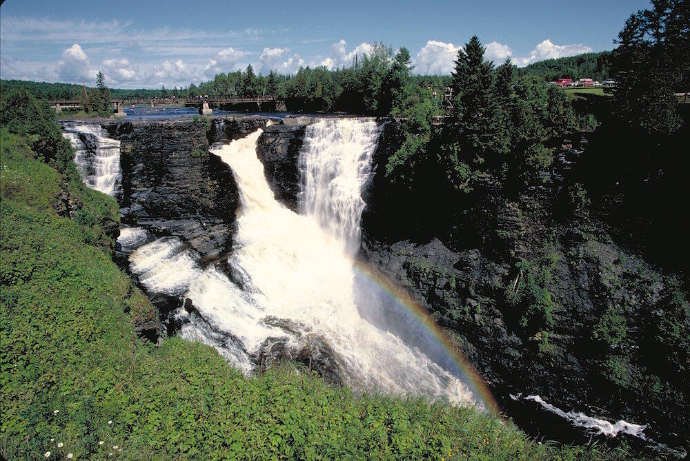 Large waterfalls with a bridge over it.