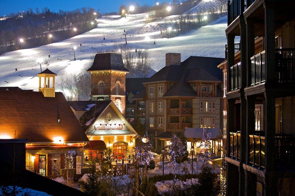 Charming Blue Mountain Resort buildings at night with ski hill.