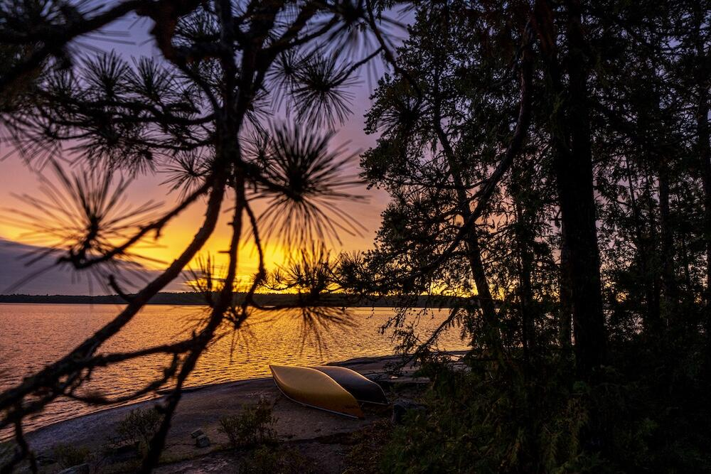 Sunset over a lake, inverted canoes along the shore.