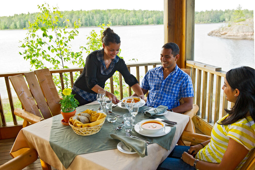 Couple sitting at a table with view of French River.