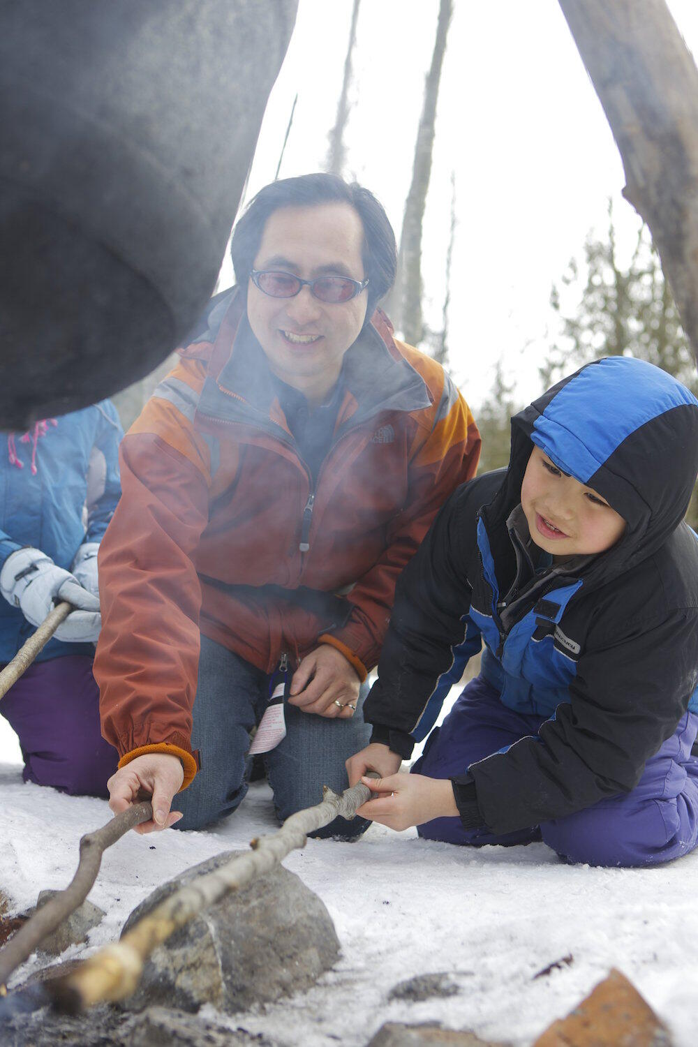Man and son cooking bannock over fire.