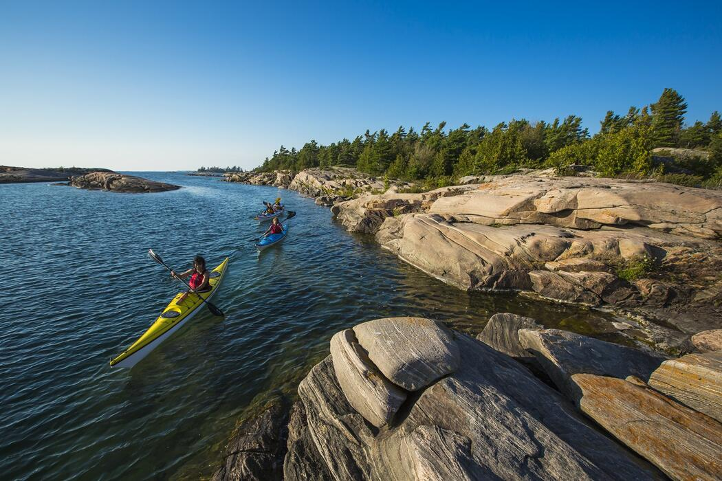 Kayakers paddling in turquoise water beside rocky island.
