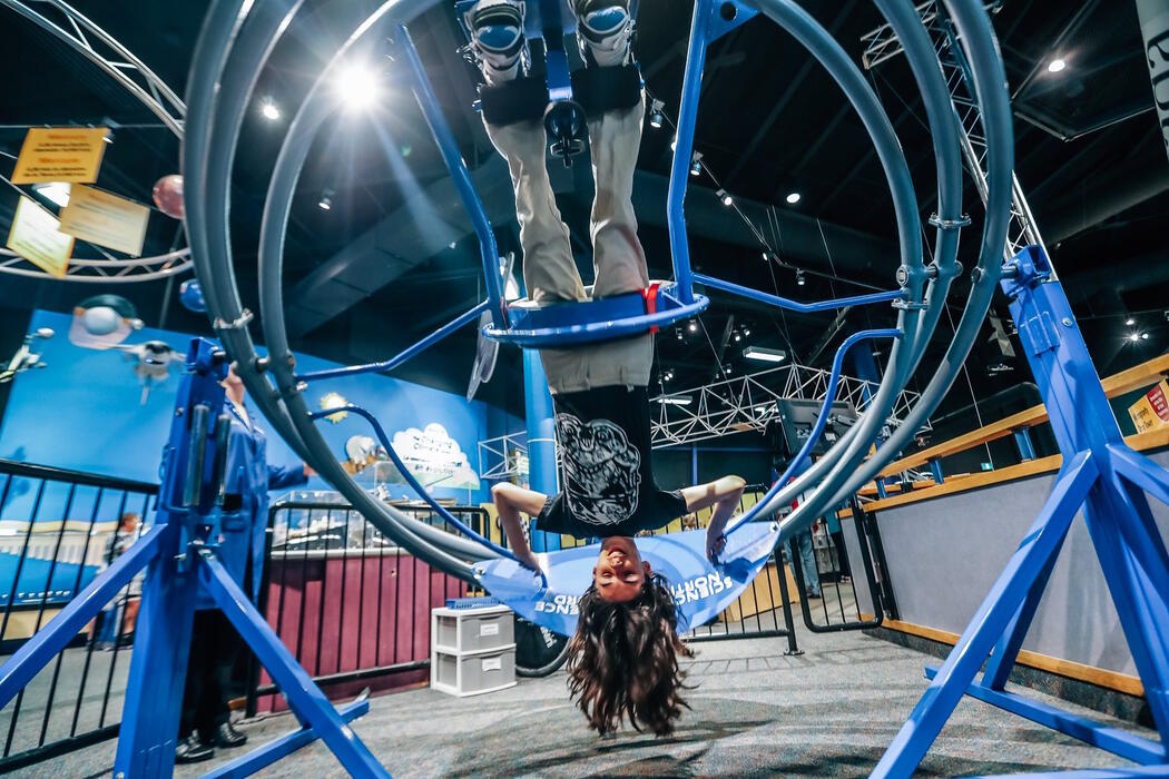 A girl hanging upside down in a contraption at Science North.