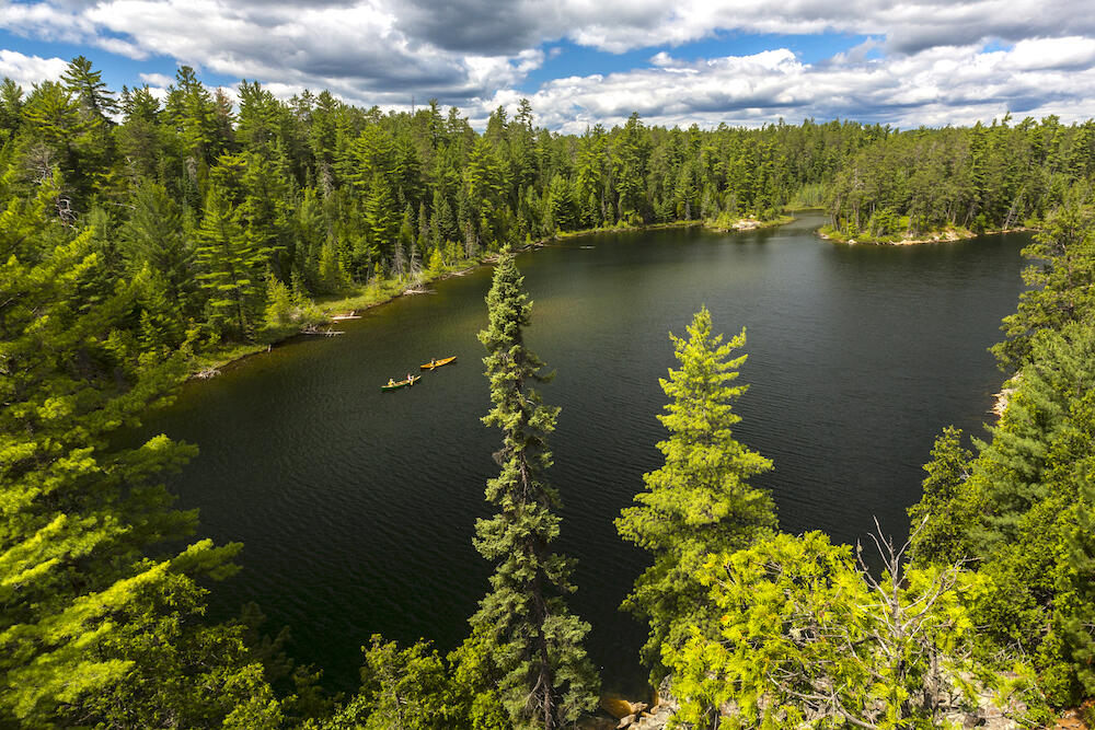 View from high point of 2 canoes travelling on lake surrounded by forest