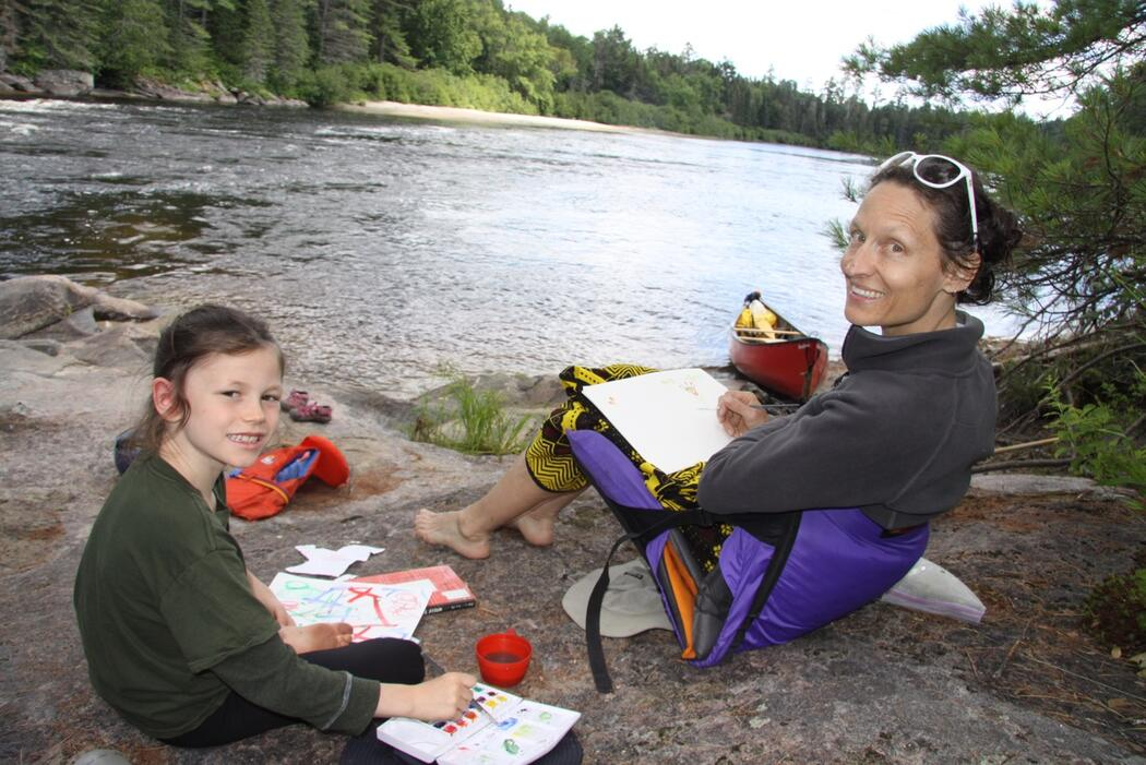 Mother and daughter sitting on rocks painting beside a river