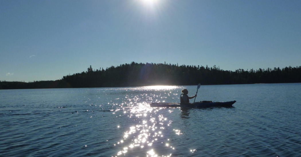 kayaker paddling on beautiful blue lake