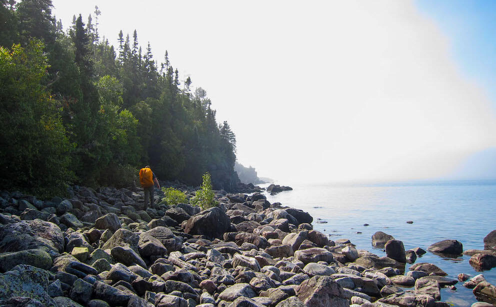 Man with backpack hiking on large boulders on shore of Lake Superior
