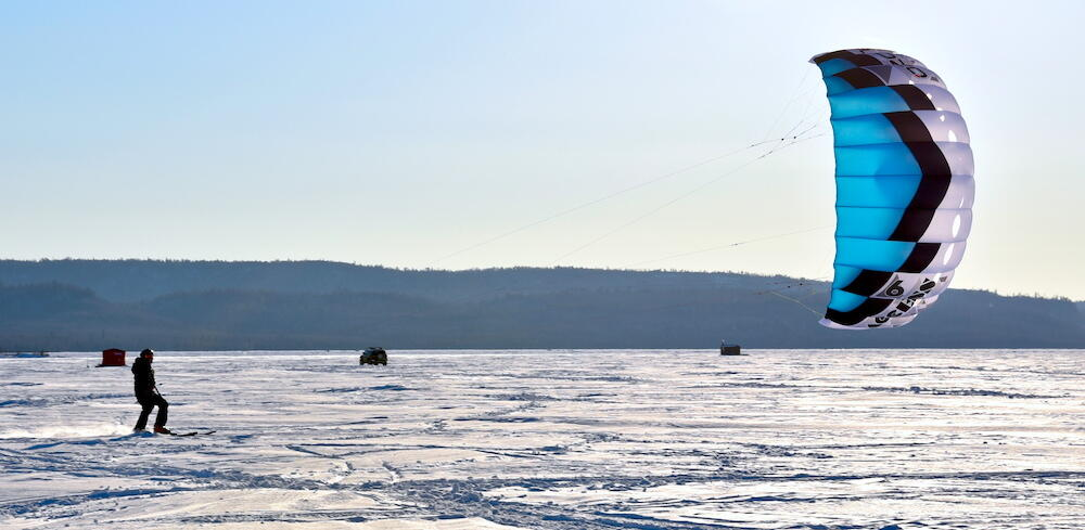 Person snowkiting on a lake with fish huts.