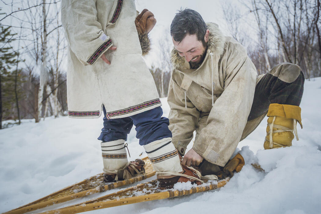 Man doing up a snowshoe harness for a woman.