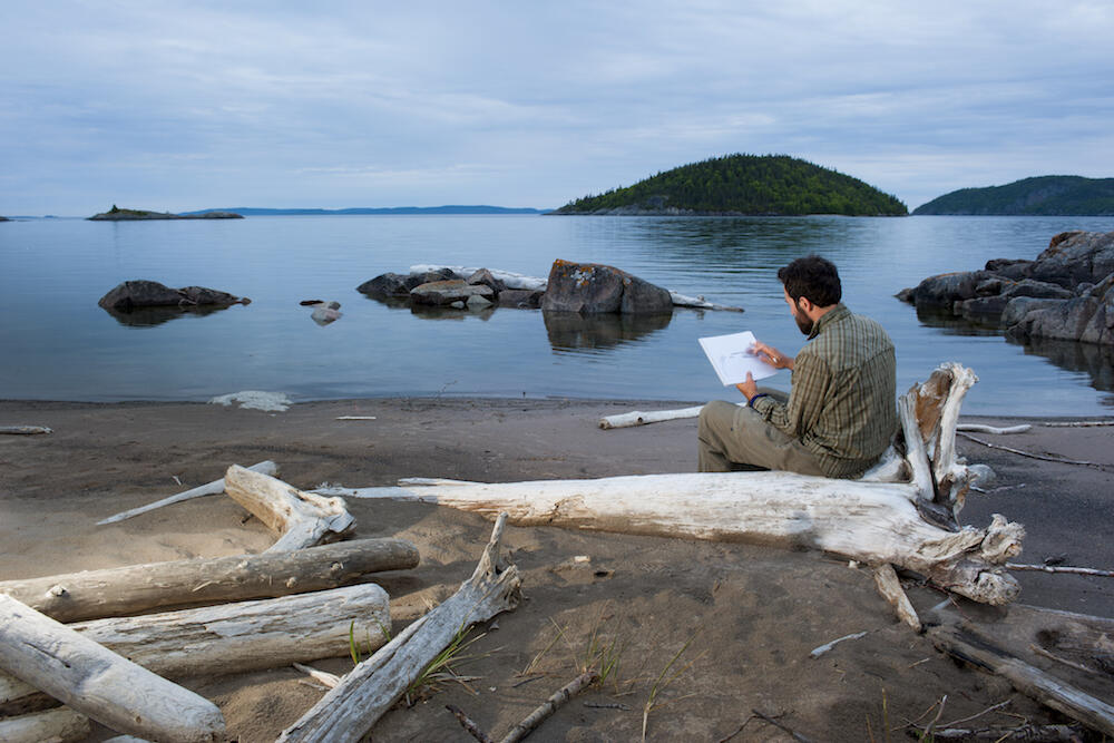 Man sketching while sitting on a beach surrounded by driftwood