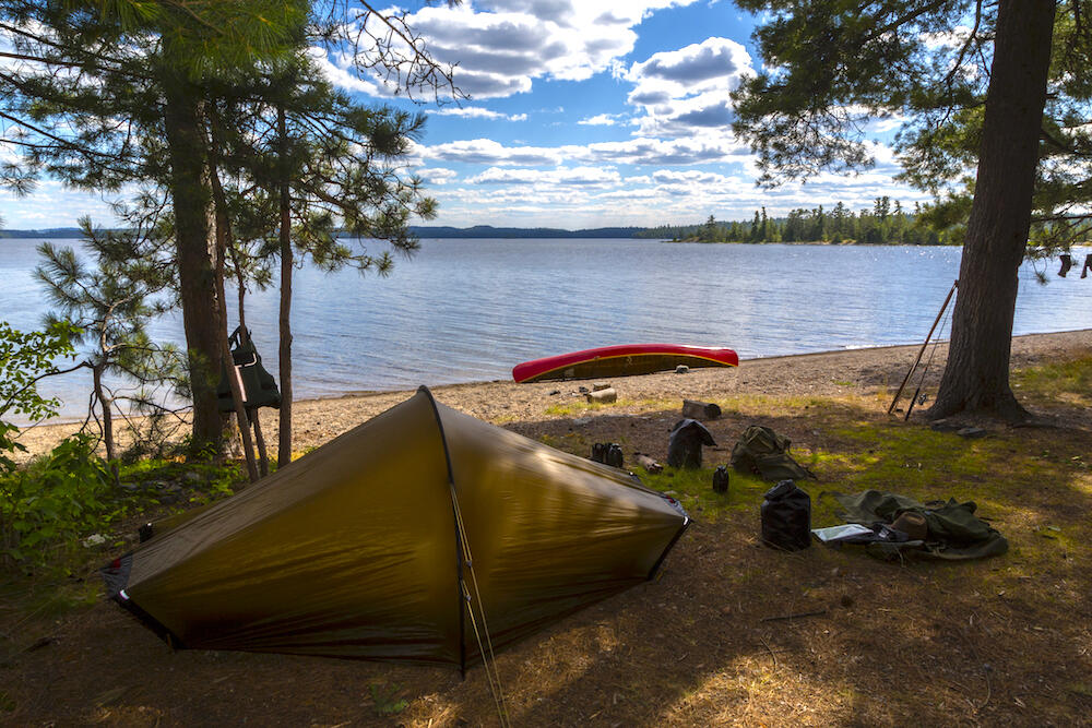 Small tent set up on edge of forest with canoe beside a lake