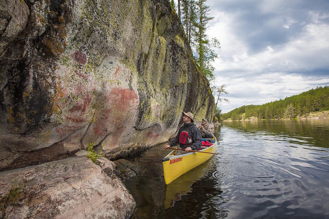 Tow men in a canoe paddling along a rock face with pictographs.