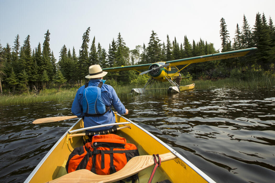 Man in bow of a canoe looking at a float plane.
