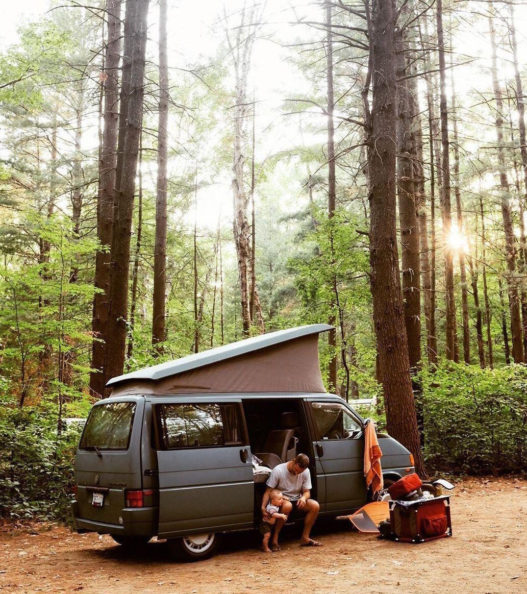 Camper van with pop-up top parked in a forest.