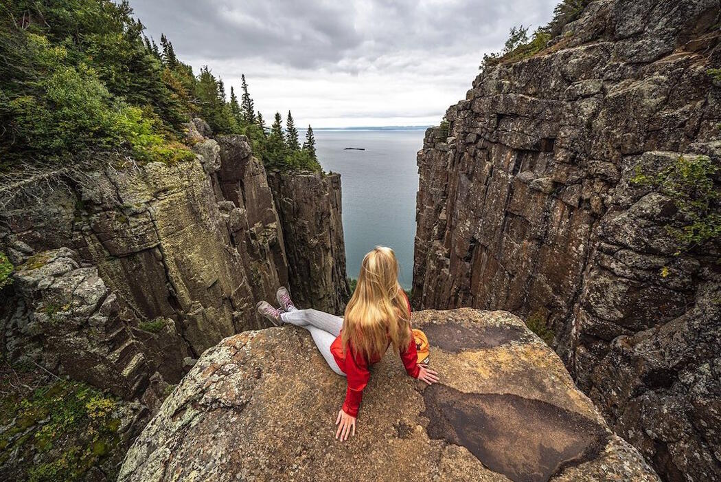 Young woman sitting on a rock at top of Sleeping Giant.