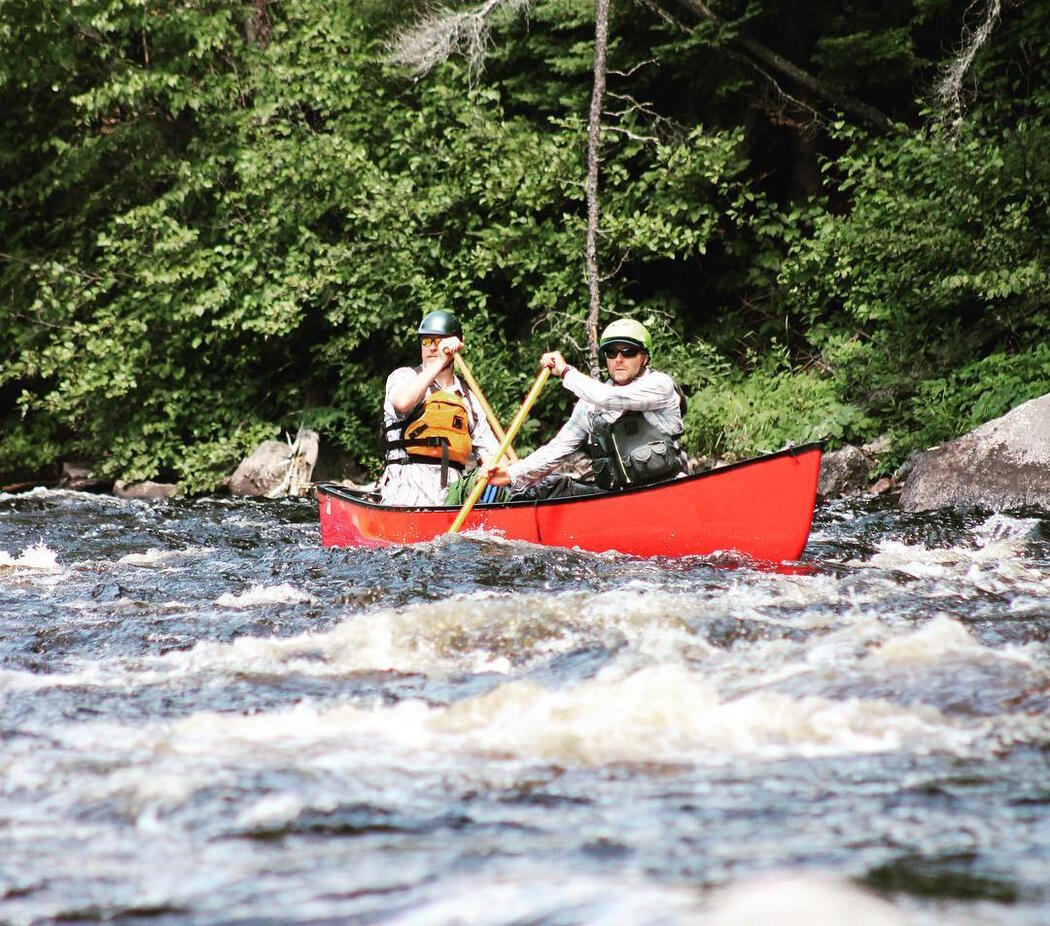 Two people paddling a red canoe in whitewater.