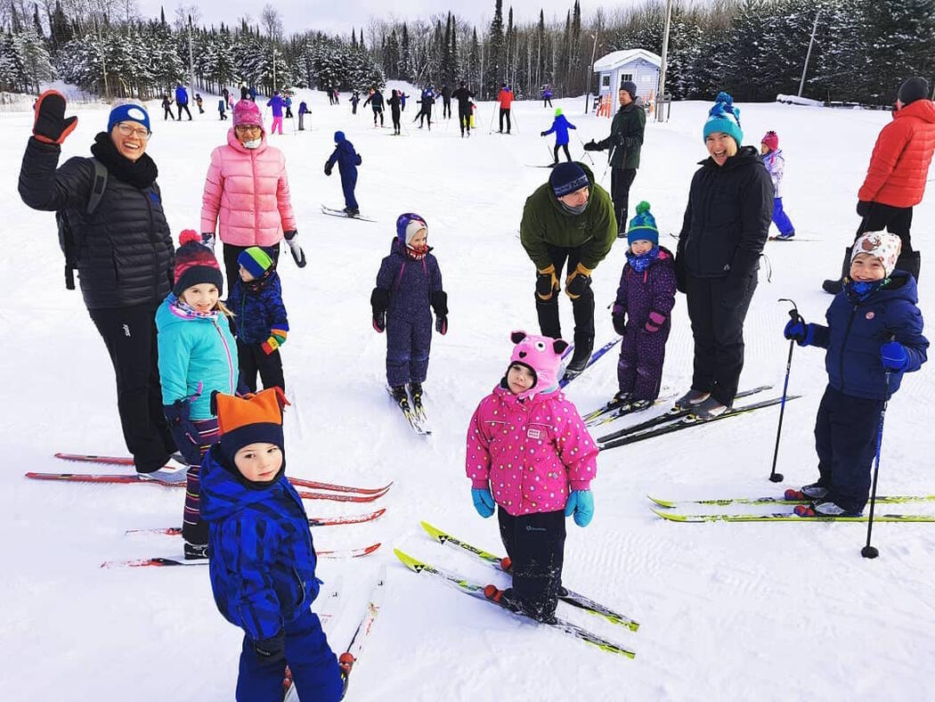 Group of children and adults on skis standing in a circle.
