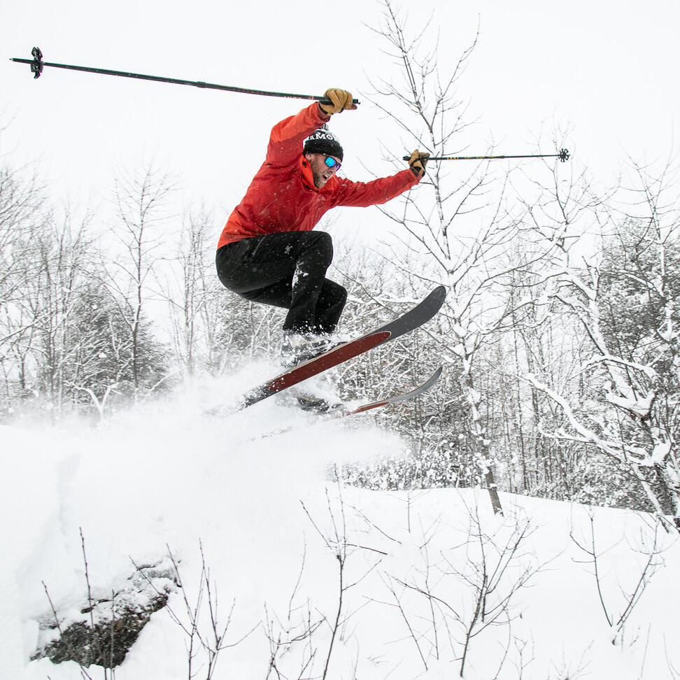 Man on skiis catching some air.