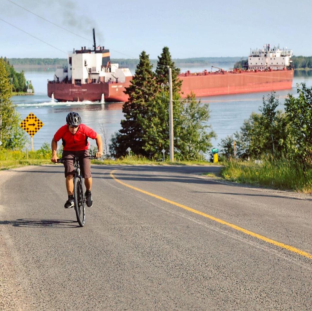 Male cyclist pedalling up a hill with a boat in background.