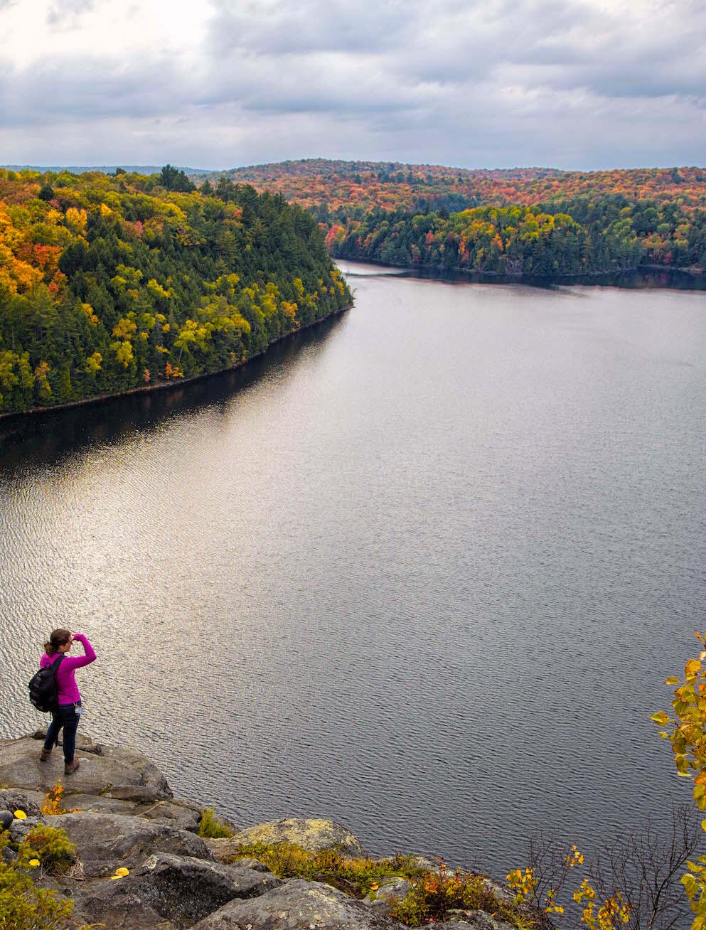 Woman standing on top of a cliff overlooking lake and colourful Fall landscape.
