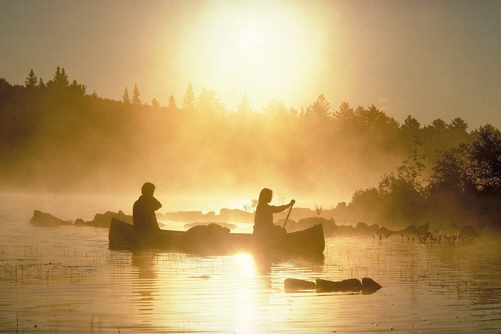 Two people paddling a canoe in early morning mist