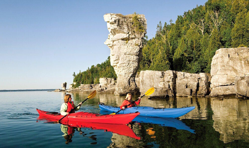 Two kayakers paddling in front of flowerpot island