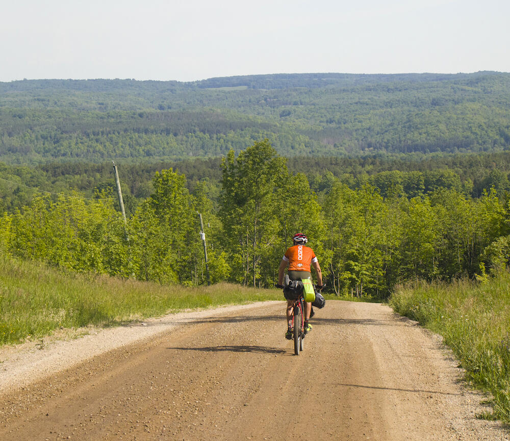 Cyclist riding on a gravel road, about to go down a big hill.