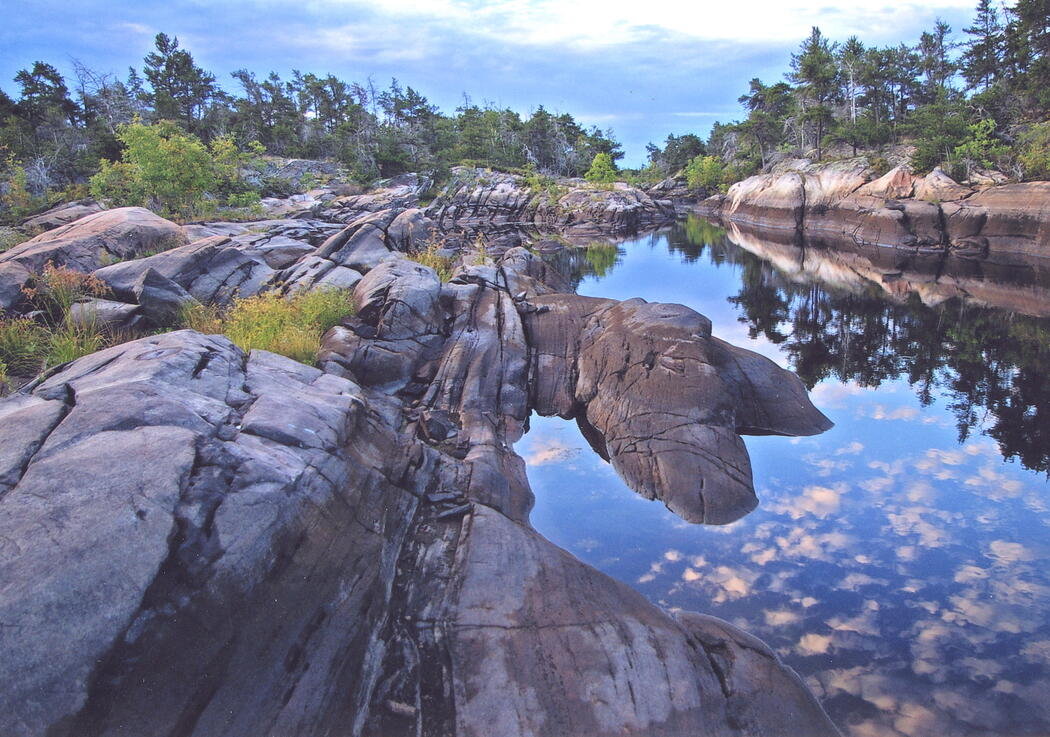 Beautiful rock lined shore of a river with reflection of clouds.