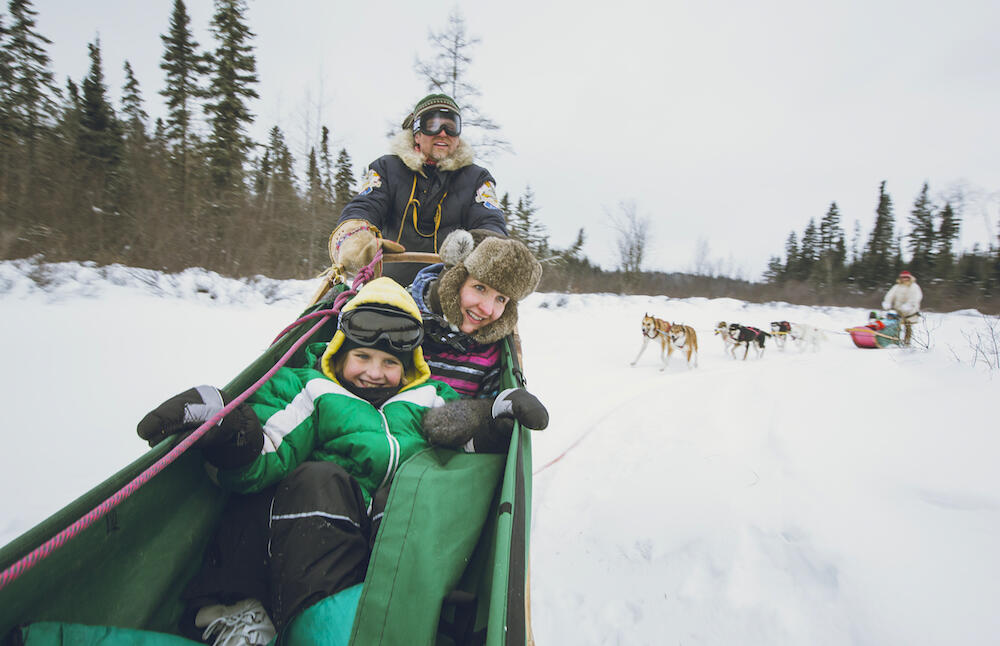 Man driving a dog sled with woman and child in basket.