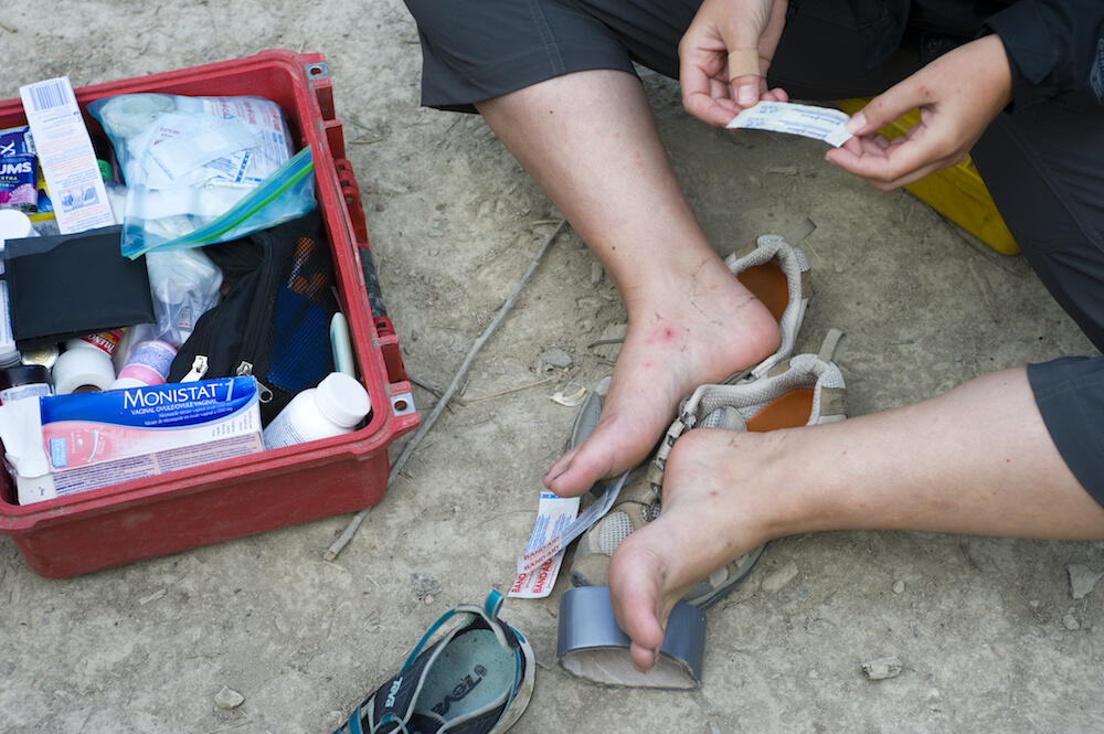 Person putting bandages on their feet