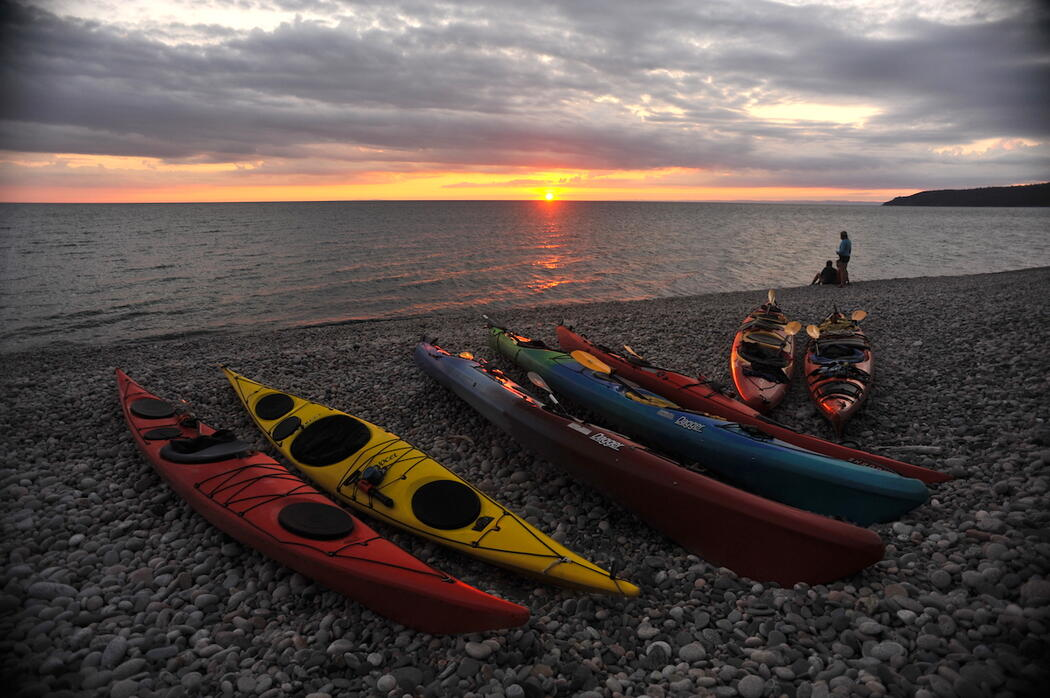 Kayaks on stone beach with sunset in background