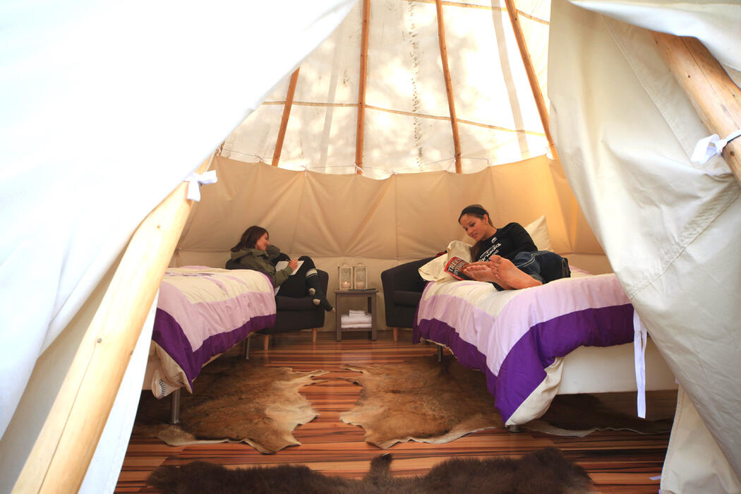 Two young women laying on beds in a teepee.