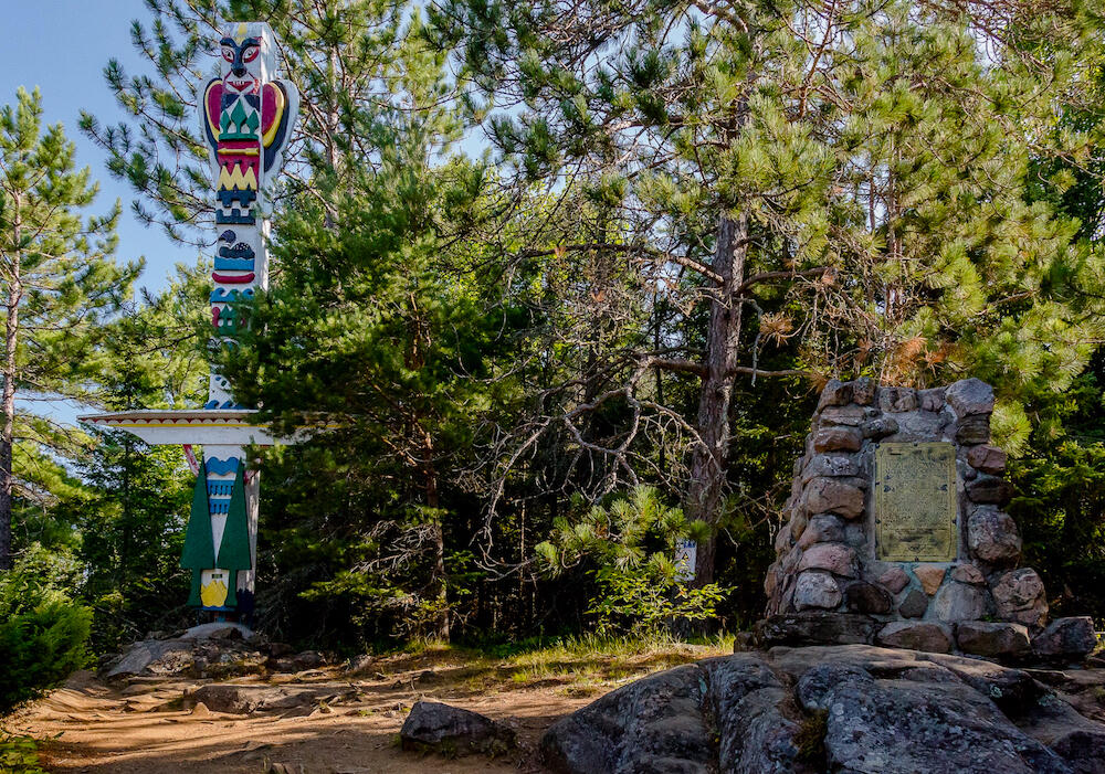 totem pole and rock cairn with Tom Thomson memorial plaque