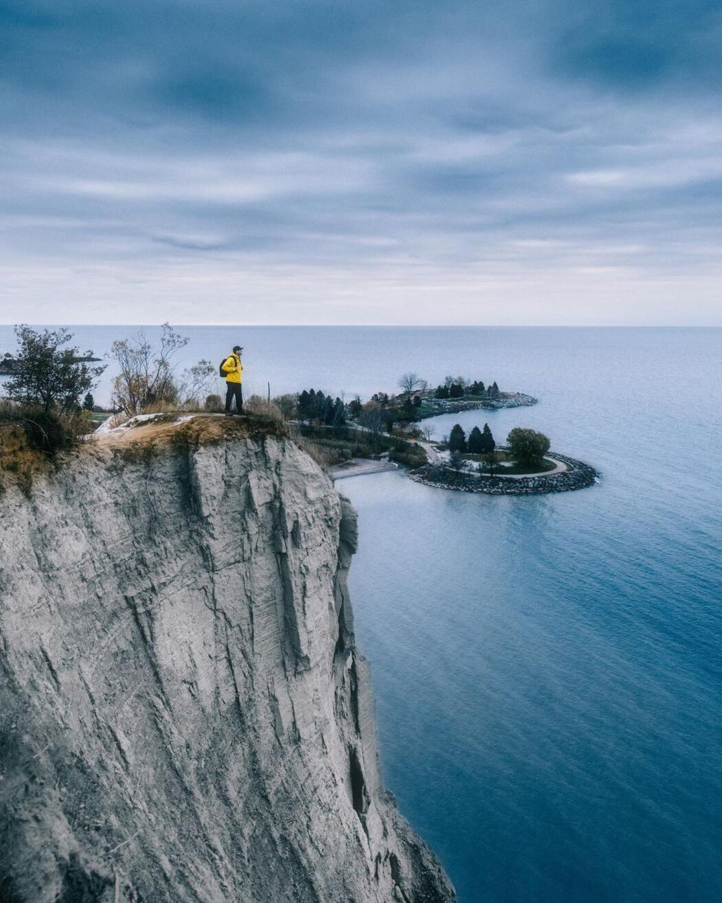 Person standing near edge of tall cliff overlooking Lake Ontario.
