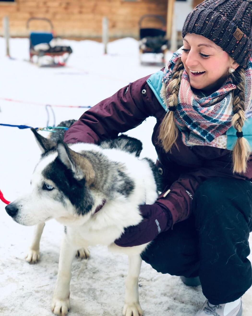 Young woman patting a blue eyed husky with dog sled in background.