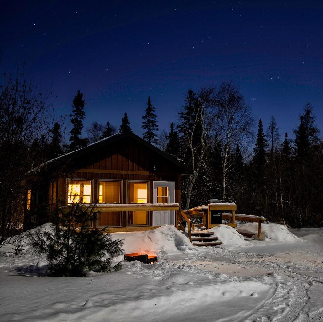 Cozy wooden cabin surrounded by snow, with lights glowing in windows.