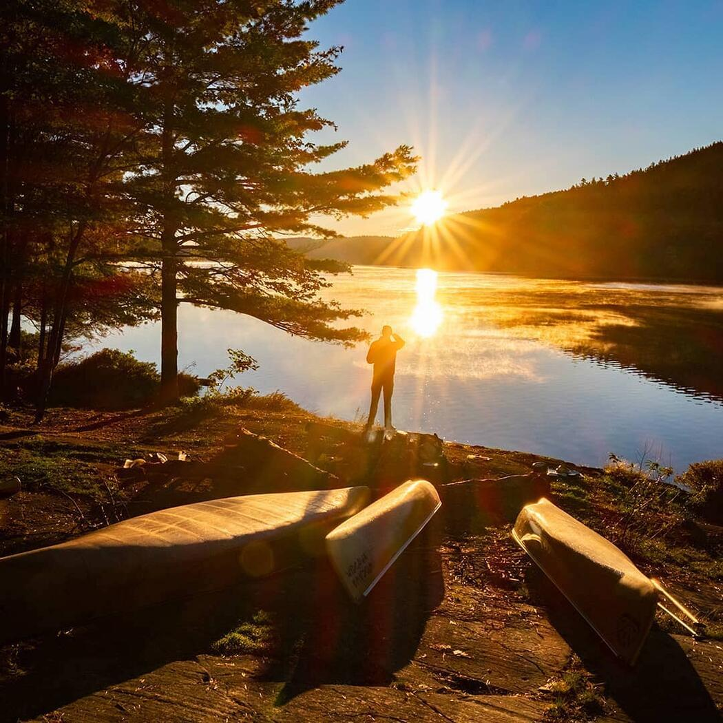 Beautiful sun burst over calm water. Man standing with canoes on beach.