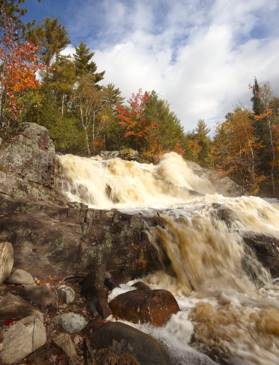 Large waterfalls flowing over rocks in autumn