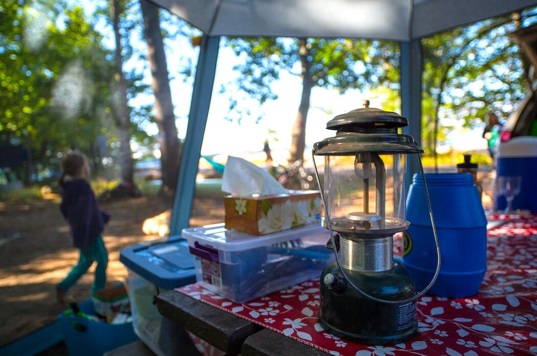 Coleman lantern and other camping gear on a picnic table.